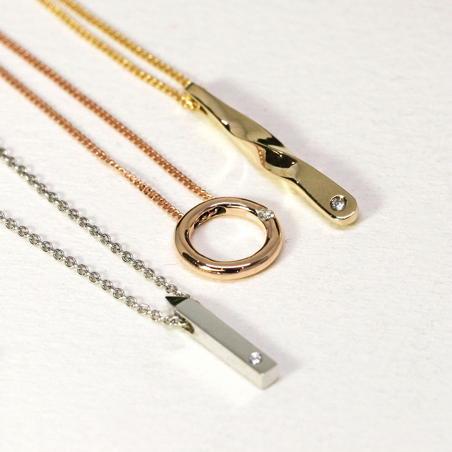 18ct gold charm necklaces, set with diamonds
