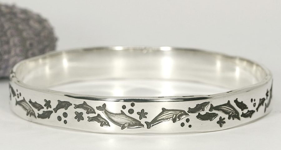 Dolphin delight handcrafted sterling silver bangle featuring dolphins frolicking
