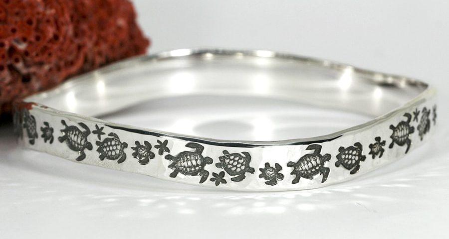 'Turtle Journey' sterling silver bangle with a hammer beat finish and a wavey profile john miller design
