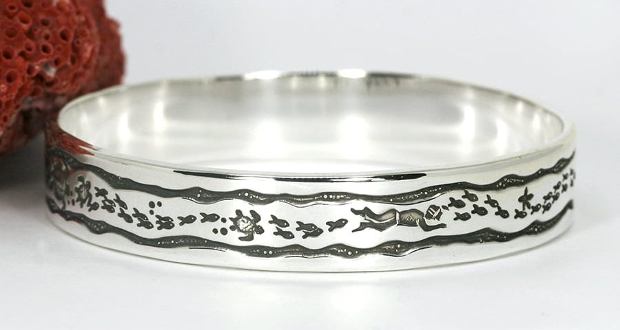 'Framed Fish' sterling silver bangle featuring diver fish turtles starfish in a wave frame john miller design