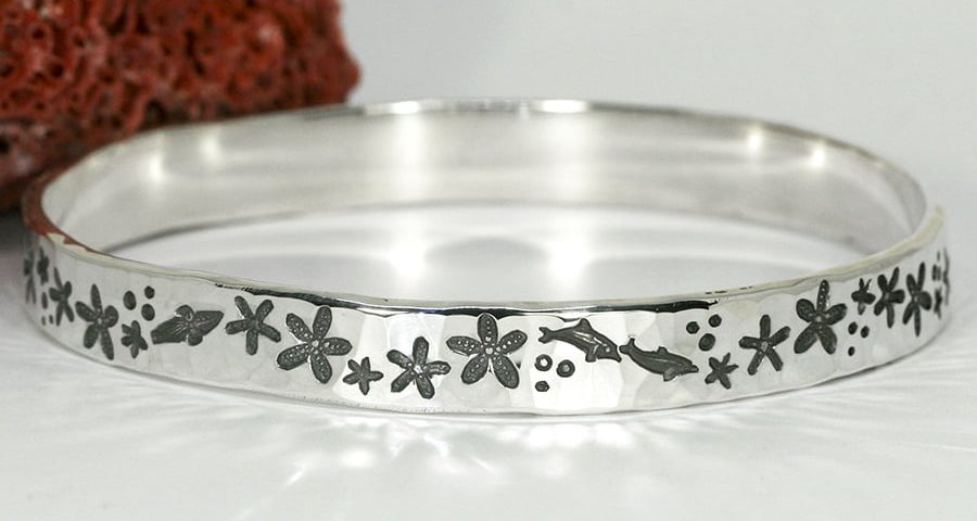 'Starfish Marine' sterling silver bangle with a hammerbeat finish featuring marine life