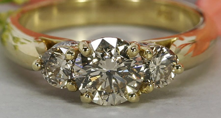 'Romance' 18ct yellow gold ring set with a cognac diamond 2 C2 diamonds white gold under setting set with 6 GSI diamonds john miller design